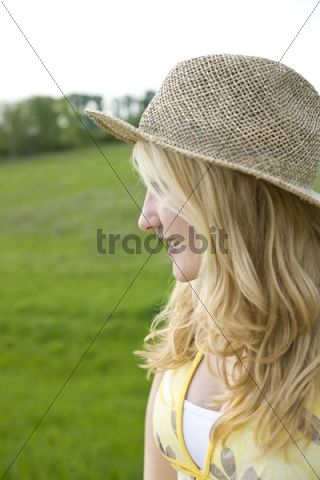Portrait of a smiling blond girl wearing a sun hat on a meadow