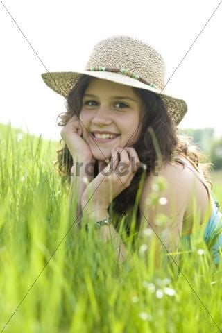 Portrait of a smiling girl wearing a sun hat while lying on a meadow