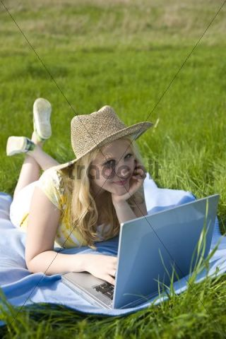Blond girl wearing a hat, smiling and working on a laptop while lying on a blanket on a meadow