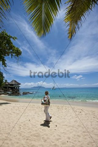 Woman walking on a beach near Glacis, Mahe Island, Seychelles, Indian Ocean, Africa