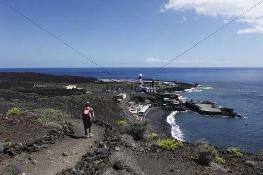 Woman with a backpack on a hiking trail near the Faro de Fuencaliente Lighthouse, La Palma, Canary Islands, Spain, Europe