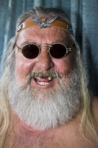Laughing old rocker with missing front teeth, long hair and beard, sunglasses and headband