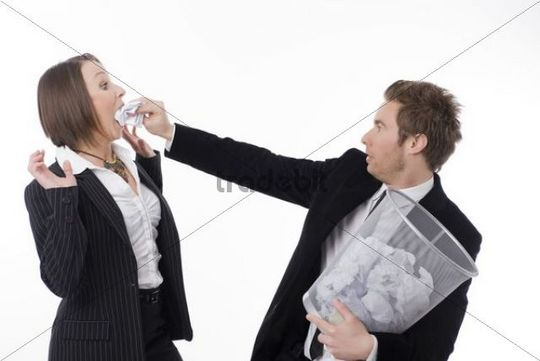 Businessman stuffing paper balls into a businesswoman´s mouth