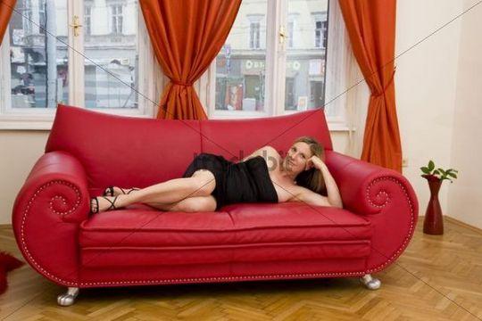 junge sexy frau liegt auf rotem sofa vor dem fenster. Black Bedroom Furniture Sets. Home Design Ideas