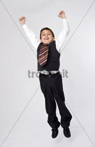Boy, 8, dressed as a businessman, jumping