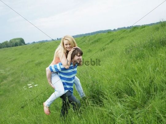 Young man carrying his girlfriend piggyback in a meadow, laughing