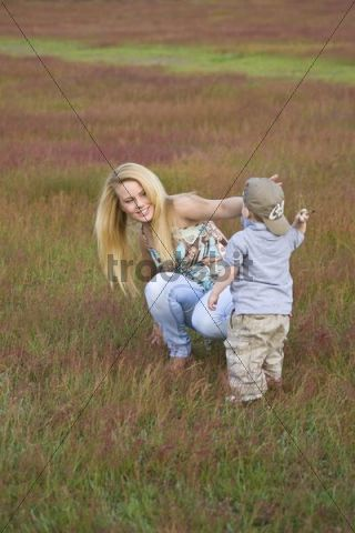 Young blonde woman and son playing on a meadow