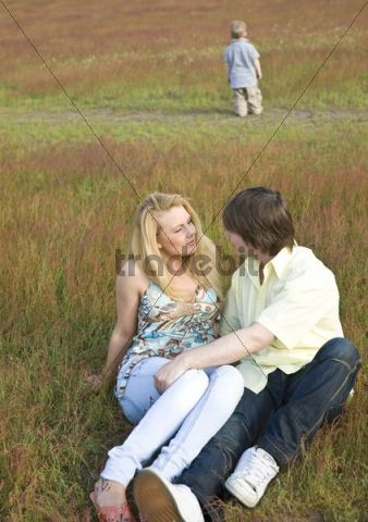 Young couple in love, sitting on a lawn