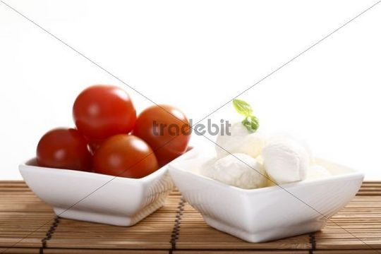 Mozzarella balls with basil and tomatoes in bowls