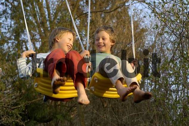 eight-year-old and ten-year-old boys swinging happy