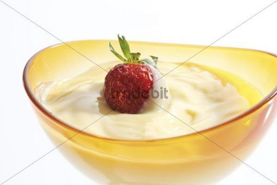 Vanilla pudding and a strawberry in a glass bowl