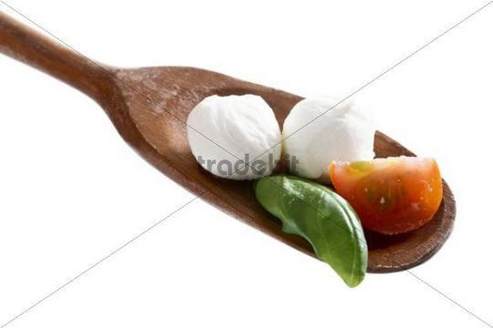 Mozzarella balls with tomato and basil on a wooden spoon