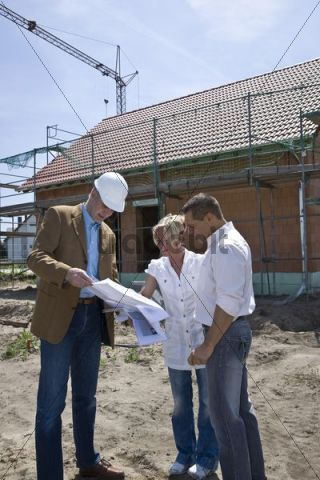 Architect and married couple looking at a construction plan in front of framing