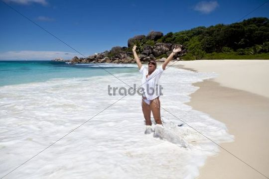 Woman standing on the beach of Grand Anse, with the typical granite rocks of La Digue, Indian Ocean, La Digue Island, Seychelles, Indian Ocean, Africa