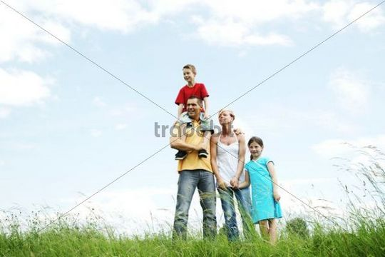 Happy family standing on a meadow