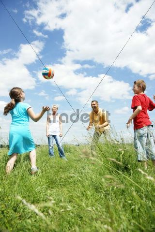 Family playing with a ball on a meadow