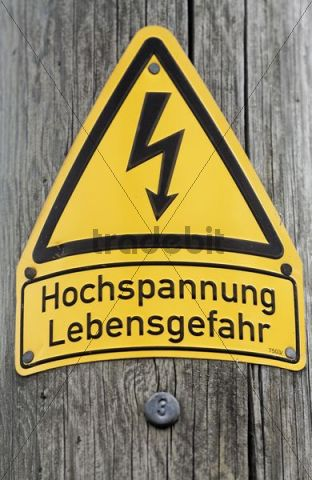 Warning sign, high tension, on a wooden power pole