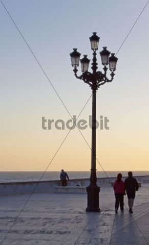 Lantern and promenader along the shore promenade in Cadiz, Andalusia, Spain, Europe