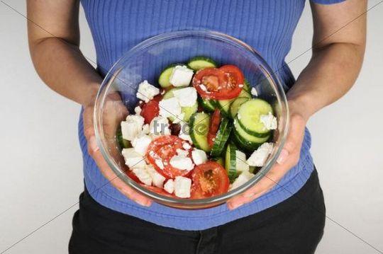 Woman presenting a freshly made Greek salad