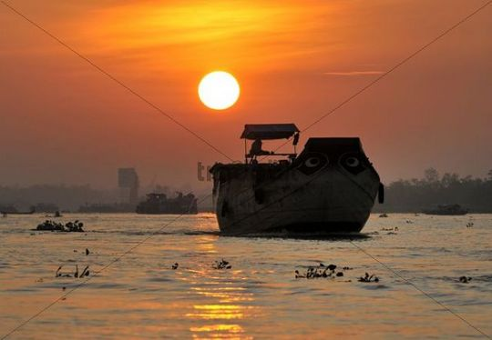 Transport ship at sunset on Mekong River, Mekong Delta, Vietnam, Asia