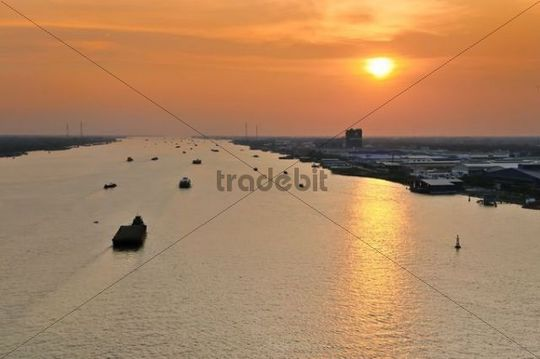 Transport boats in the last evening light during sunset on the Mekong River, My Tho, Mekong Delta, Vietnam, Asia