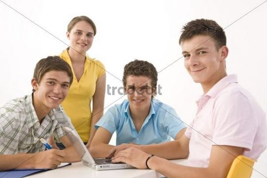 Three boys and a girl working on a computer