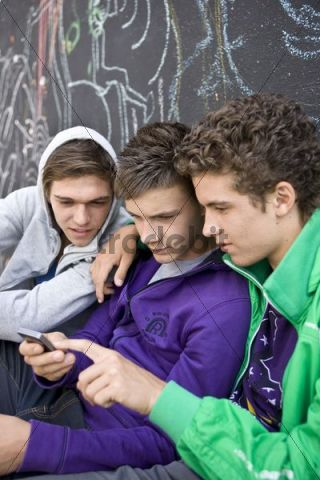 Three boys sitting in front of a wall, sending a text message