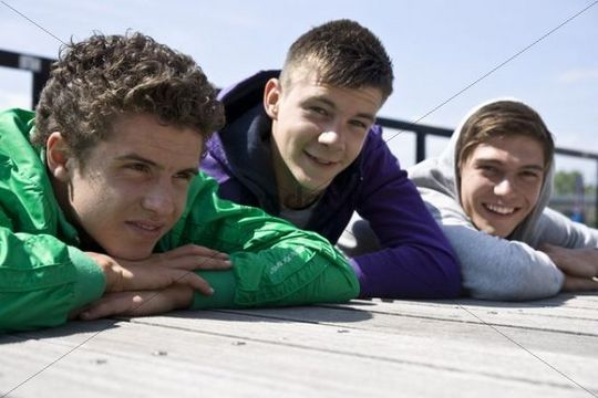Three guys lying on the floor, relaxing in the sun
