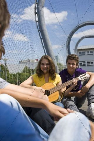 Girl playing the guitar, three boys listening
