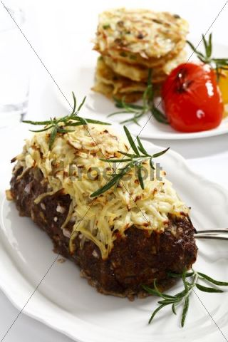 Meatloaf with baked cheese and rosemary in front of potato roestis with roasted capsicum