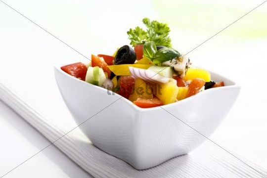 Greek salad with onions, tomatoes, capsicum, feta and olives in a small salad bowl