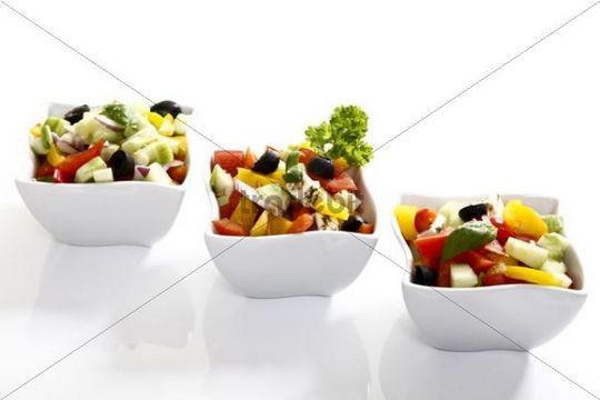 Greek salad with onions, tomatoes, capsicum, feta and olives in small bowls