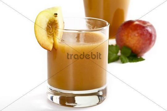 Glass of peach juice with a slice of peach