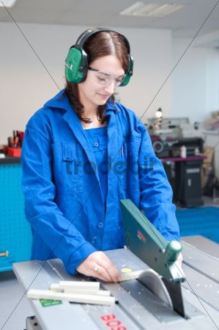 Young woman working at a circular saw bench
