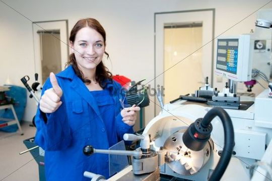 Young woman working at a lathe, thumbs up