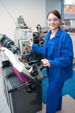 Young woman working at a band-saw
