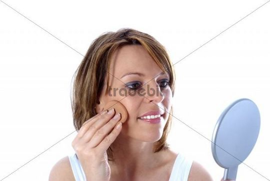 Young woman powdering her face in front of a mirror