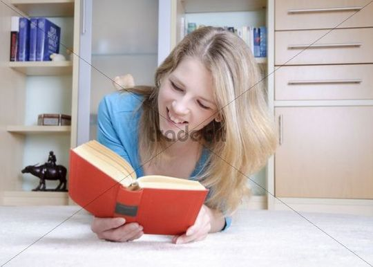 Woman lying on the floor, reading a book