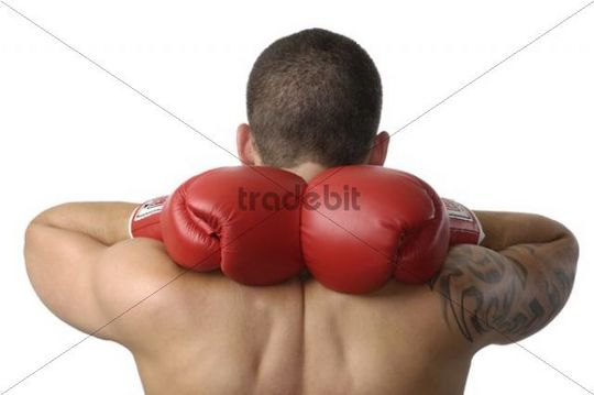 Young man, kickboxer, wearing red boxing gloves with hands behind his neck
