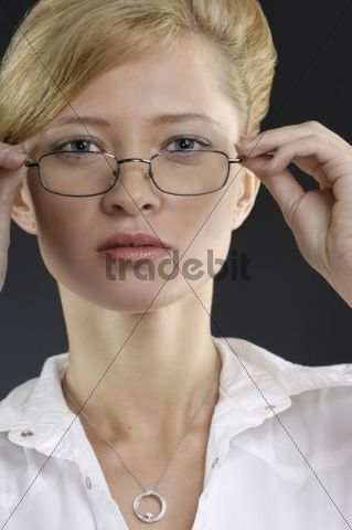 Portrait of a young businesswoman looking over her eyeglasses