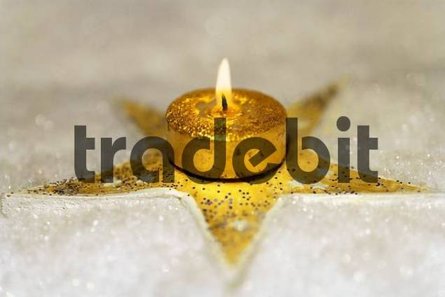 golden star in snow with golden candle