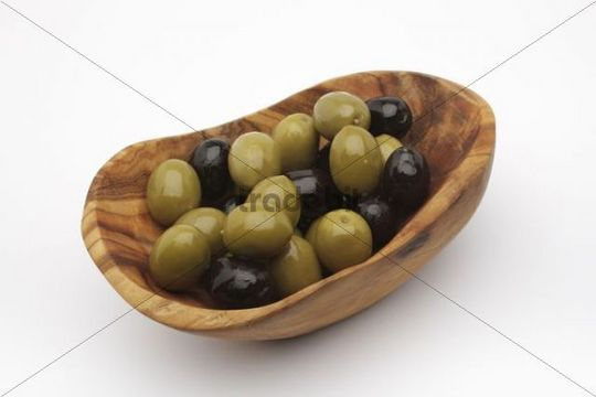 Green and black olives in a bowl made of olive wood
