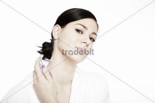 Young woman spraying on perfume