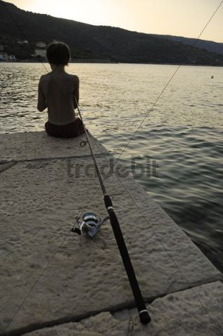 Boy, 11, seen from behind, seated while fishing on a pier, Bay of Valun, Cres Island, Croatia, Europe