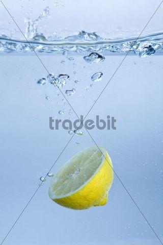 Half lemon falling into water