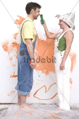 Young couple painting a wall