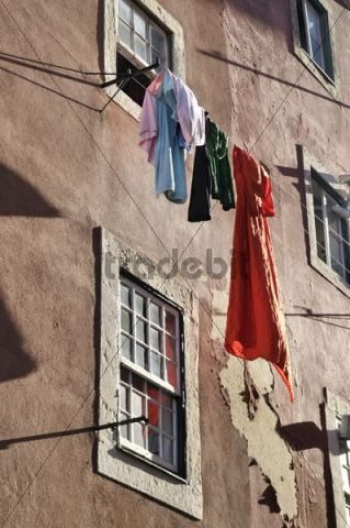 Laundry hanging to dry on a line in front of a house with crumbling plaster walls in the district of Alfama, Lisbon, Portugal, Europe