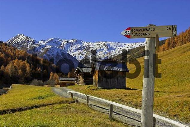 signposts and wooden huts in the Vallung valley end of the Rojen valley, South Tyrol, Italy
