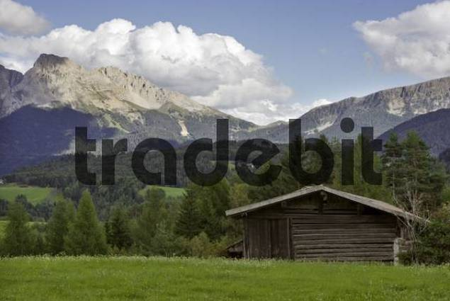 wooden hut on a meadow behind the mountain range Rosengarten, Deutschnofen, Eggen valley, South Tyrol, Italy