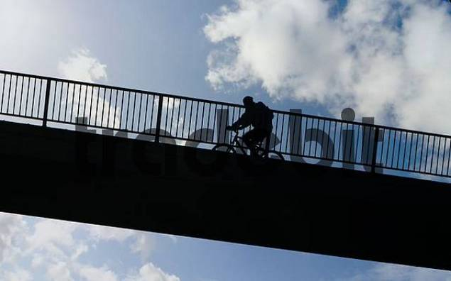 cyclist riding his bike up a bridge, with cloudy sky in the background, composing
